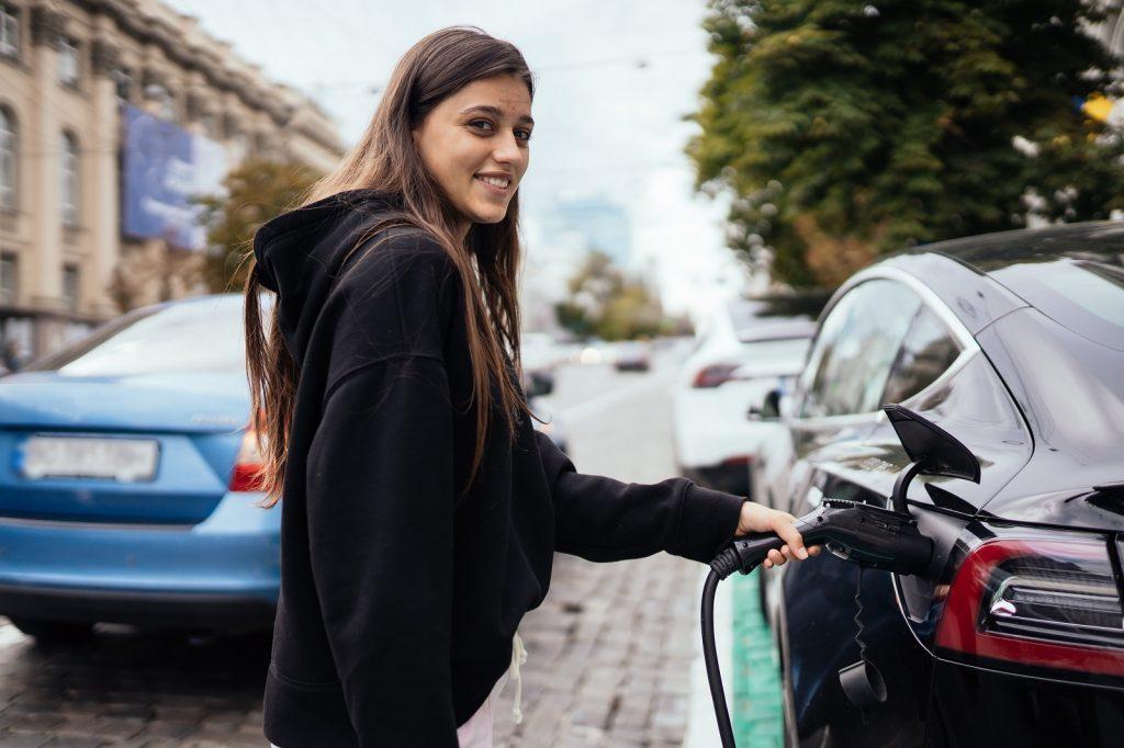 mulher recarregando carro elétrico